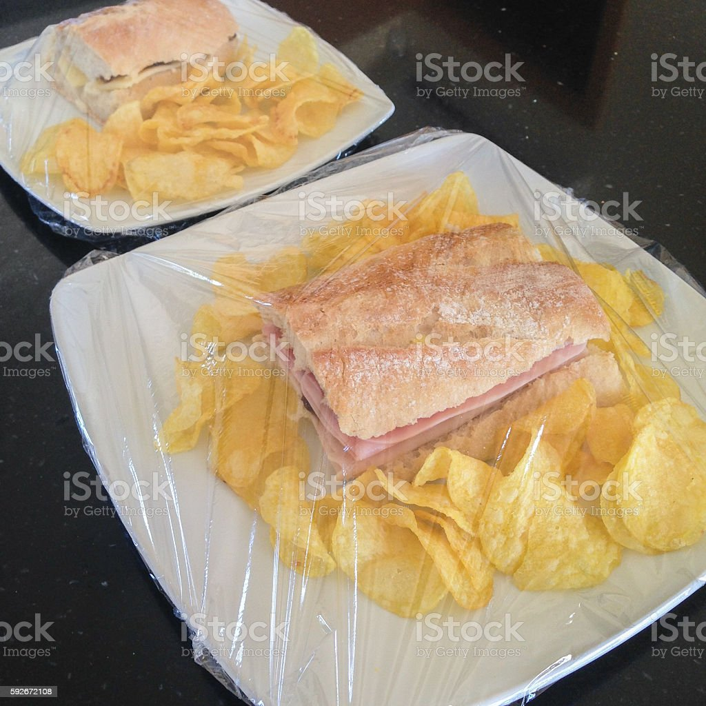 Baguette sandwich on a plate covers in plastic wrap. royalty-free stock photo & Baguette Sandwich On A Plate Covers In Plastic Wrap Stock Photo ...