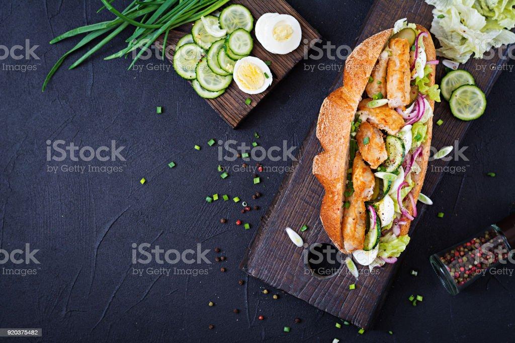 Baguette-Sandwich mit Salat, eingelegte Zwiebeln, Fisch und Ei verlässt. Ansicht von oben – Foto