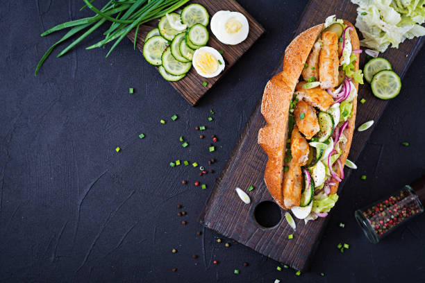 baguette sandwich with fish, egg, pickled onions and lettuce leaves. top view - panino ripieno foto e immagini stock