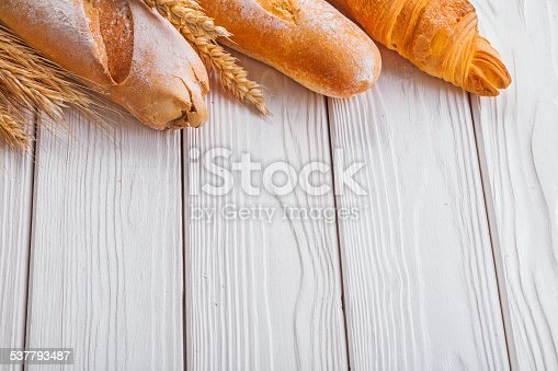 baguettes and croissant wheat ears on wooden boards with copyspace