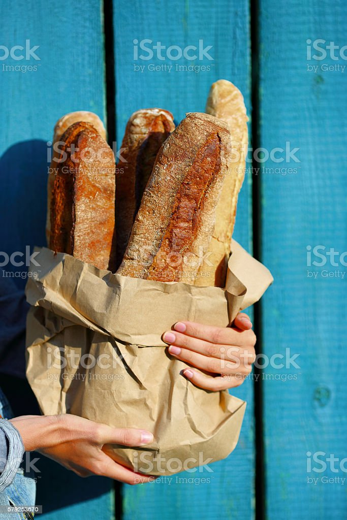 Baguettes. Paper bag with baguette in hands of woman closeup stock photo