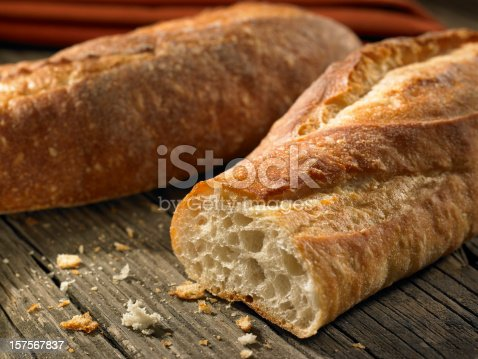 Two fresh baguettes on a wood background. Selective focus is on the cut loaf.