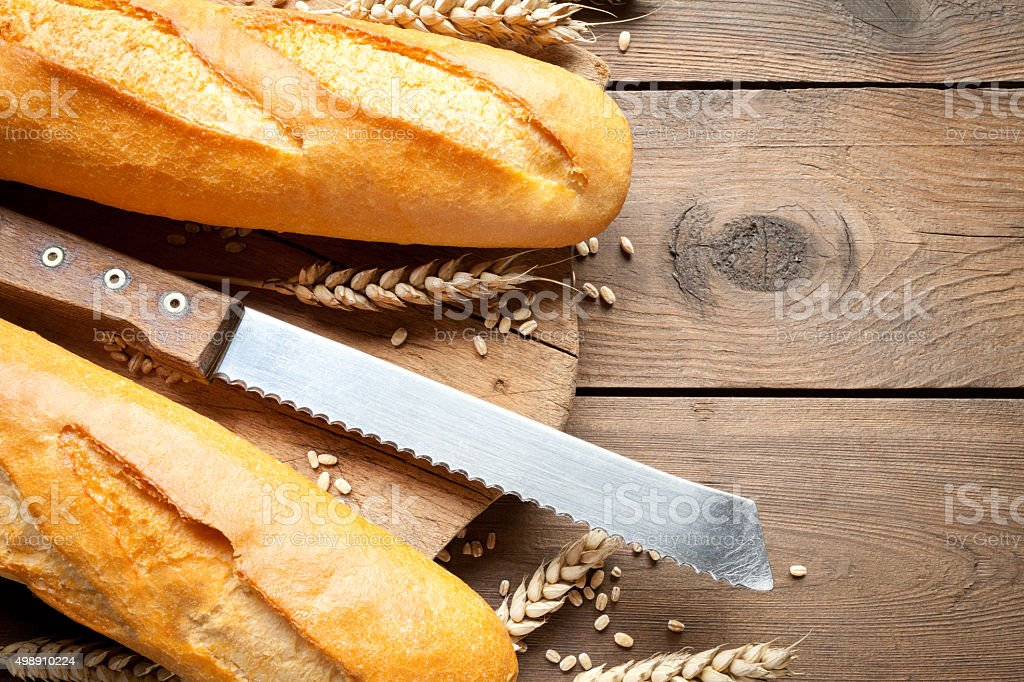 Baguettes with knife and cutting board stock photo