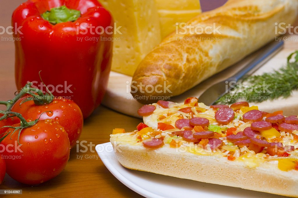 Baguettes with pepperoni on the plate and ingredients royalty-free stock photo