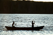 Alcobaça, Brazil - July, 03 2014: Two men rowing a small wooden boat through a canal just before the sun goes down at Barra do Itanhém beach in Alcobaça city, Bahia state