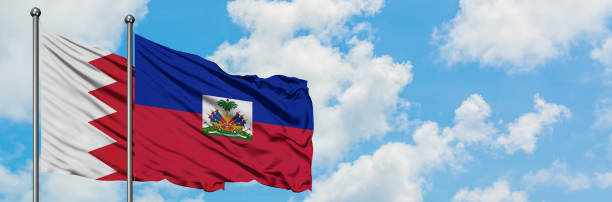 Bahrain and Haiti flag waving in the wind against white cloudy blue sky together. Diplomacy concept, international relations. Bahrain and Haiti flag waving in the wind against white cloudy blue sky together. Diplomacy concept, international relations. Haiti Flag stock pictures, royalty-free photos & images
