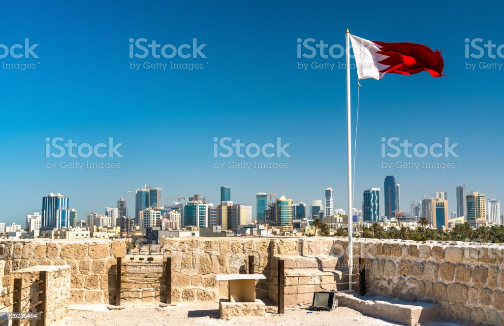 Bahrain Flag with skyline of Manama at Bahrain Fort. A UNESCO World Heritage Site stock photo