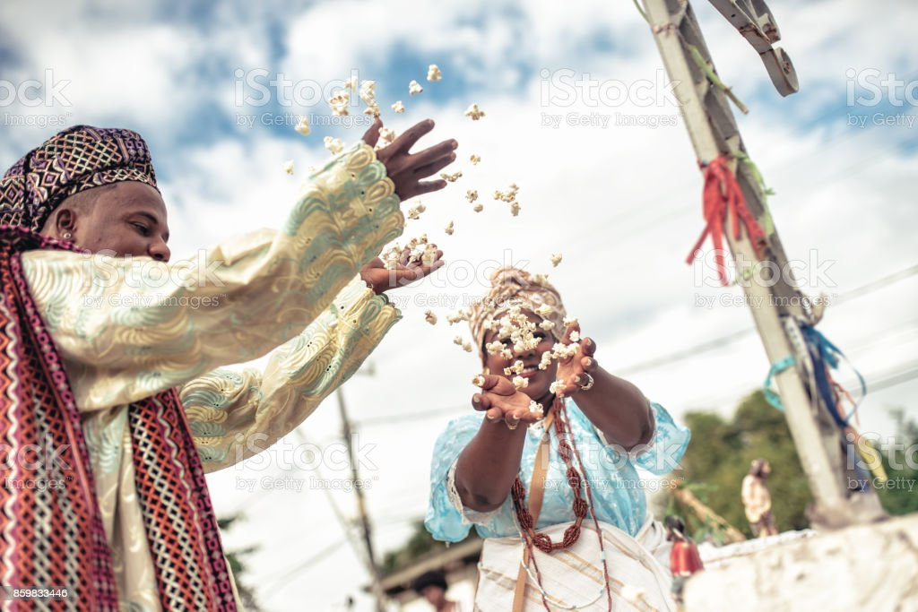 baiana and baiano in traditional religious costume throwing popcorn in the air stock photo
