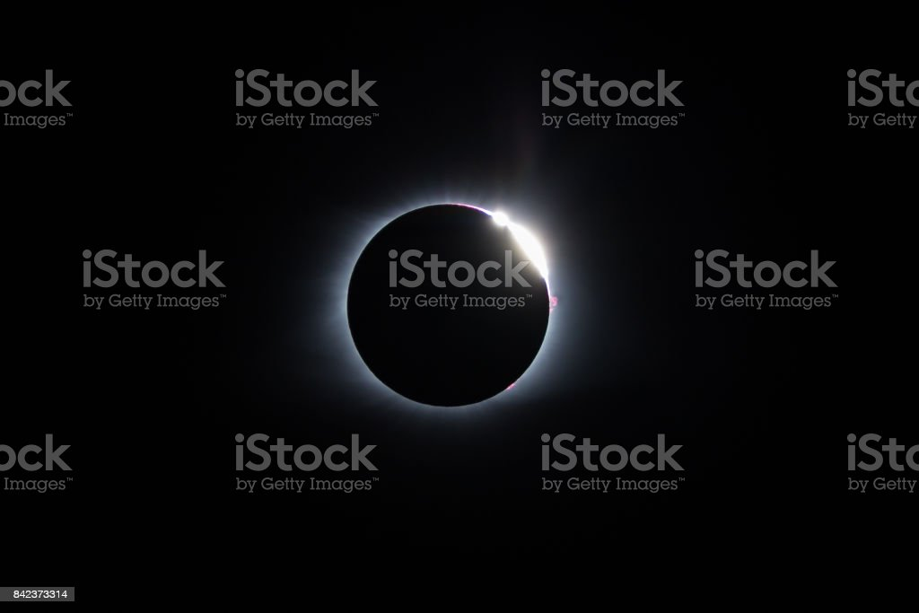 Bailey's Beads - 2017 Total Solar Eclipse The sun begins to reappear after totality during the 2017 total solar eclipse with the Bailey's beads effect being seen through the peaks and valleys of the moon. A large solar prominence can be seen on the right limb of the sun. Astronomy Stock Photo