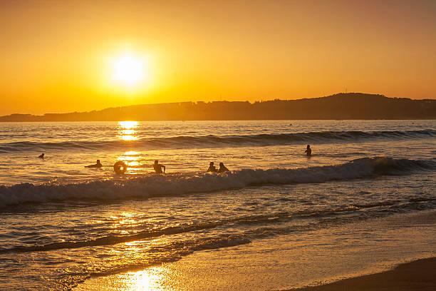 Bañistas y surfistas en la playa de La Lanzada al atardecer stock photo