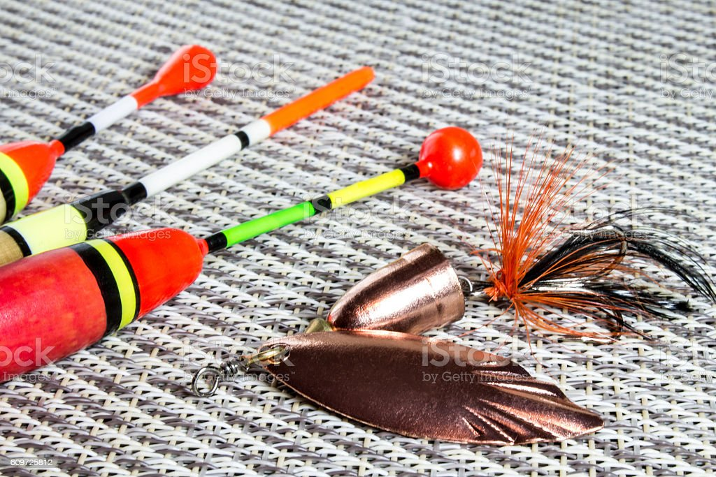 bait, wobbler and fishing accessories on a  net background stock photo