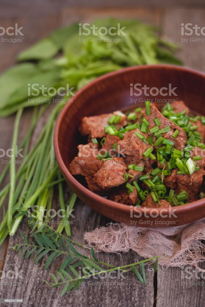 baked and tomato sauce veal with green onion on a clay plate zbiór zdjęć royalty-free