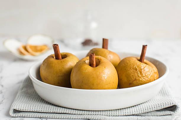 baked apple with cinnamon stick - bratäpfel stock-fotos und bilder