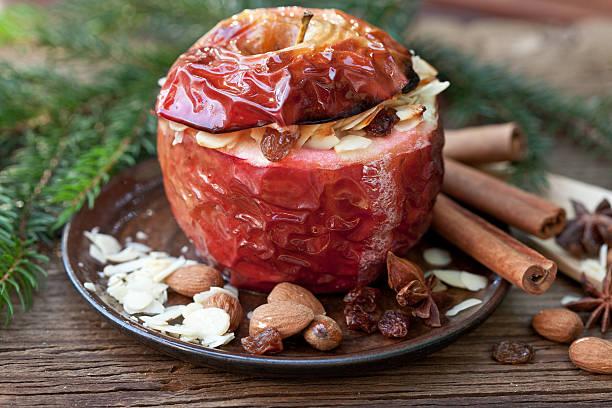 bratapfel mit gewürzen und fir branch - bratäpfel stock-fotos und bilder