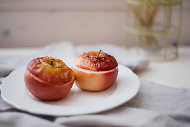 baked apples on a white background - bratäpfel stock-fotos und bilder