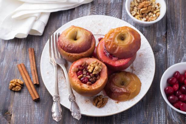 Bratäpfel gefüllt mit Preiselbeeren, Walnüssen und Honig mit Zimt auf einem Holztisch – Foto