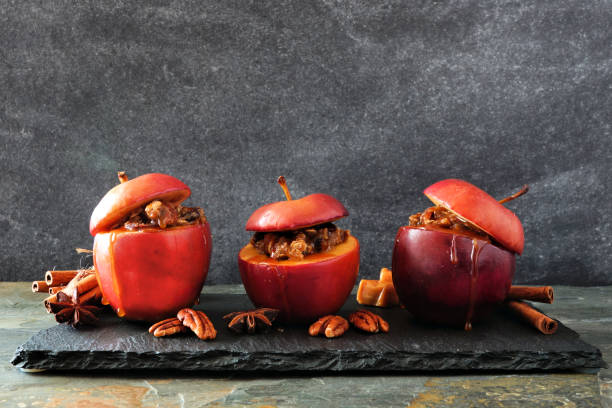 bratäpfel mit karamell, brauner zucker und und nüsse auf einem dunklen hintergrund - zimt pekannüsse stock-fotos und bilder