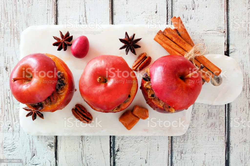 Baked apples with caramel, brown sugar and and nuts, top view on white wood stock photo