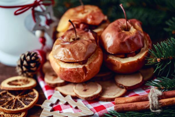 bratäpfel mit zimt auf rustikalen hintergrund. herbst oder winter dessert. nahaufnahme foto eine leckere bratäpfel mit weihnachtsdekoration - bratäpfel stock-fotos und bilder