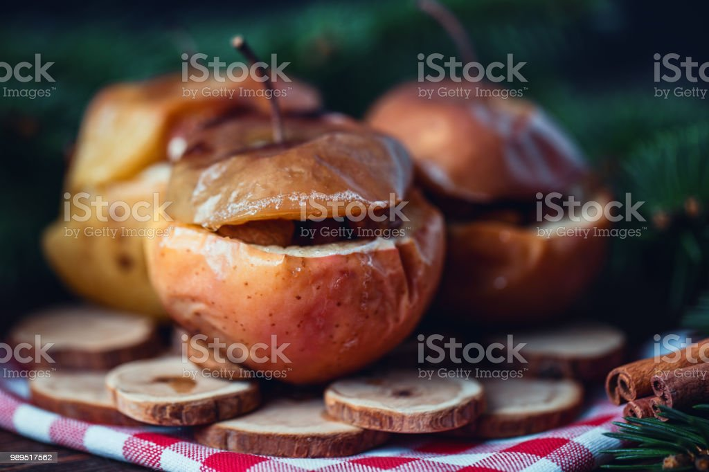 Baked apples with cinnamon on rustic background. Autumn or winter dessert. Closeup photo of a tasty baked apples with christmas decoration stock photo