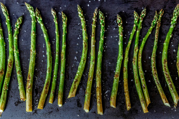 Baked asparagus on a dark background. stock photo