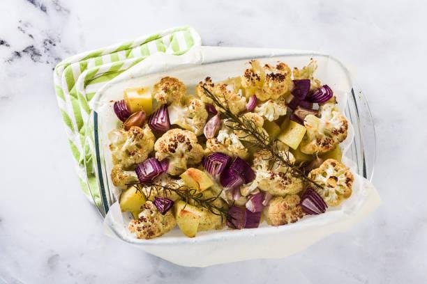 herbstgemüse in einem glas backblech gebacken: blumenkohl, kartoffeln und zwiebeln. gebackene ernährung in den ofen. - gebackener blumenkohl stock-fotos und bilder