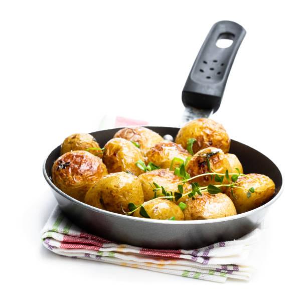 bakad baby potatis i en stek panna isolerad på vitt - frying pan bildbanksfoton och bilder