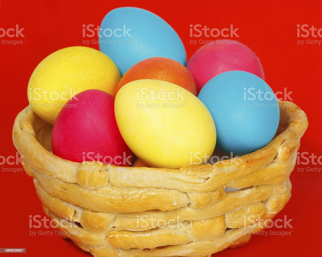 Baked basket with Easter colored eggs on a red background royalty-free stock photo