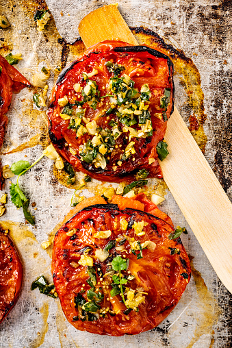 Overhead view of two thick slices of beefsteak or heirloom tomatoes cooked with; garlic, ginger, coriander and sesame seeds. Vertical format, with some copy space photographed on a baking tray just out of the oven.