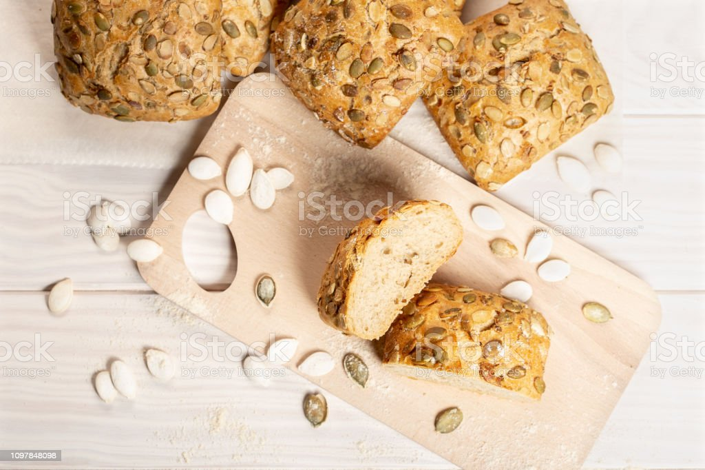 Baked bread with pumpkin seeds on cutting board. Top view stock photo