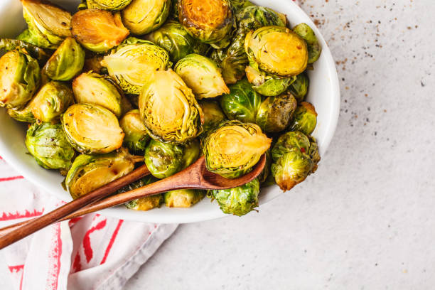 Baked brussels sprouts on a white plate, copy space, top view. stock photo