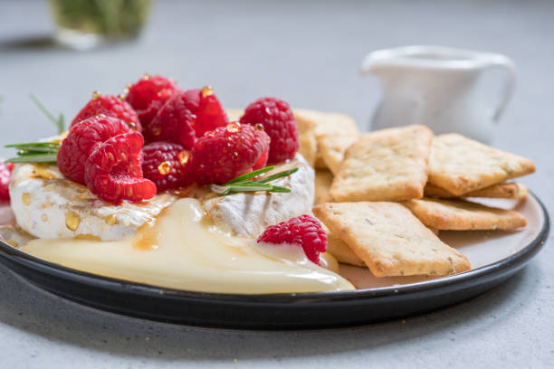 baked camembert cheese with raspberry - baked brie stock photos and pictures