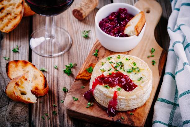 baked camembert with cranberry sauce and thyme - baked brie stock photos and pictures