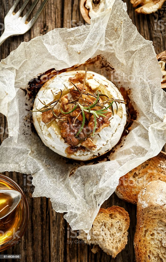 Baked Camembert with walnuts, honey  and rosemary on wooden table stock photo