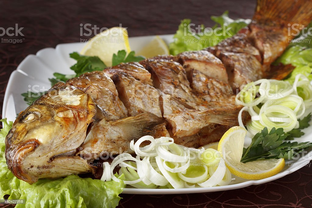 Baked carp fish with vegetables entirely. Traditional Christmas menu. stock photo