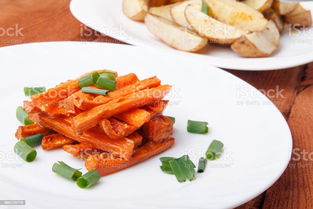 Baked carrots and potatoes with green onions on a white plate. royalty-free stock photo