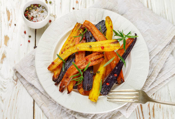 baked carrots with rosemary, coarse sea salt and pepper. colorful vegetables and spices. vegetarian dish. selective focus - warzywo korzeniowe zdjęcia i obrazy z banku zdjęć