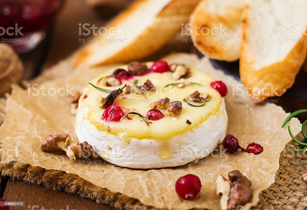 Baked cheese Camembert with cranberries and nuts stock photo