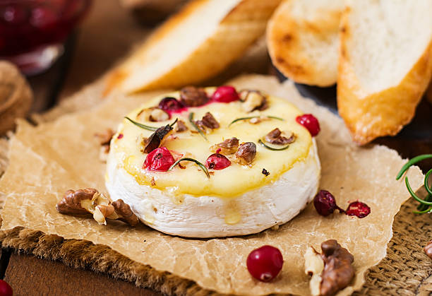 baked cheese camembert with cranberries and nuts - baked brie stock photos and pictures