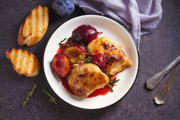 Pollo al horno y ciruelas en salsa de jengibre, miel y vino tinto con tomillo - foto de stock