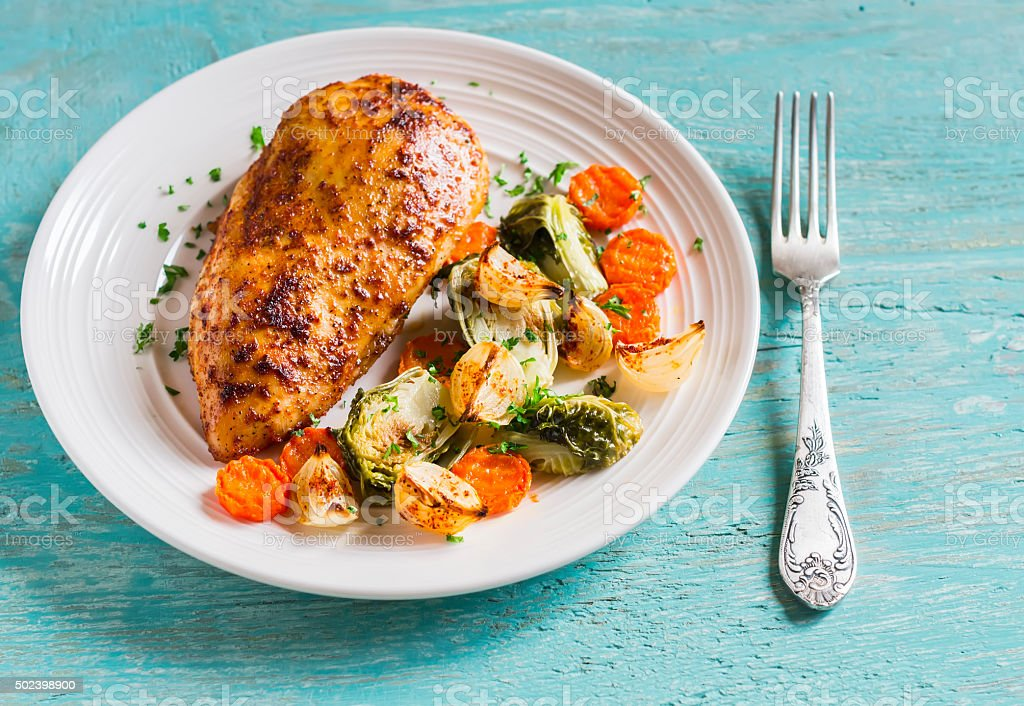 baked chicken breast with brussels sprouts, onions and carrots stock photo