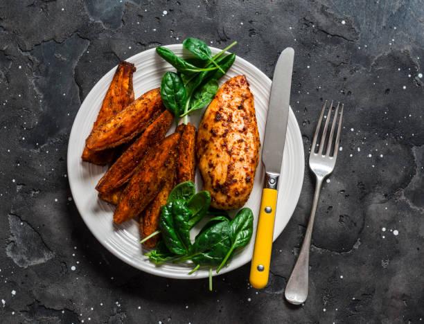 Gebackene Hähnchenbrust mit Süßkartoffeln und Spinat auf dunklem Hintergrund, Ansicht von oben. Ausgewogenes gesundes Mittagessen – Foto
