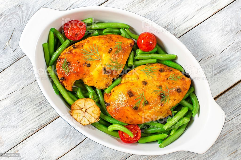 baked chicken breasts with green beans and tomatoes, top view stock photo