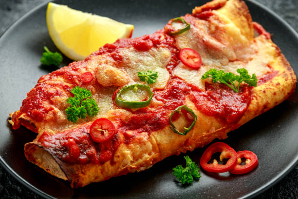 Baked Chicken fillets enchiladas with courgette, salsa sauce and cheese served with lemon wedges and chilies stock photo