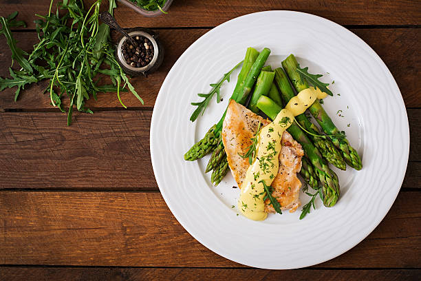 Baked chicken garnished with asparagus and herbs Baked chicken garnished with asparagus and herbs. Top view main course stock pictures, royalty-free photos & images