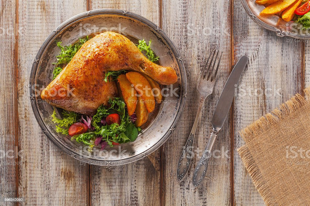 Baked chicken leg, served with roasted potatoes and vegetables. Lizenzfreies stock-foto