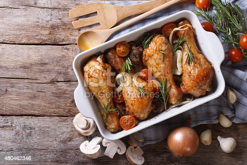 istock Baked chicken legs with mushrooms and vegetables. horizontal top 480462346