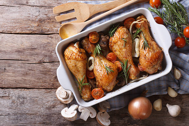 Baked chicken legs with mushrooms and vegetables. horizontal top Baked chicken legs with mushrooms and vegetables. horizontal view from above drumstick stock pictures, royalty-free photos & images