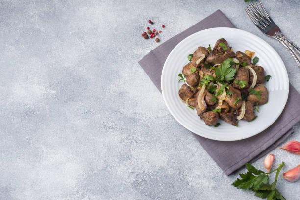 gebackene hühnerleber mit zwiebeln auf einem teller - innereien stock-fotos und bilder