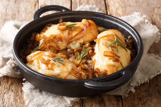 Baked chicken onion breast with cheese in a spicy wine sauce close-up in a pan. horizontal stock photo